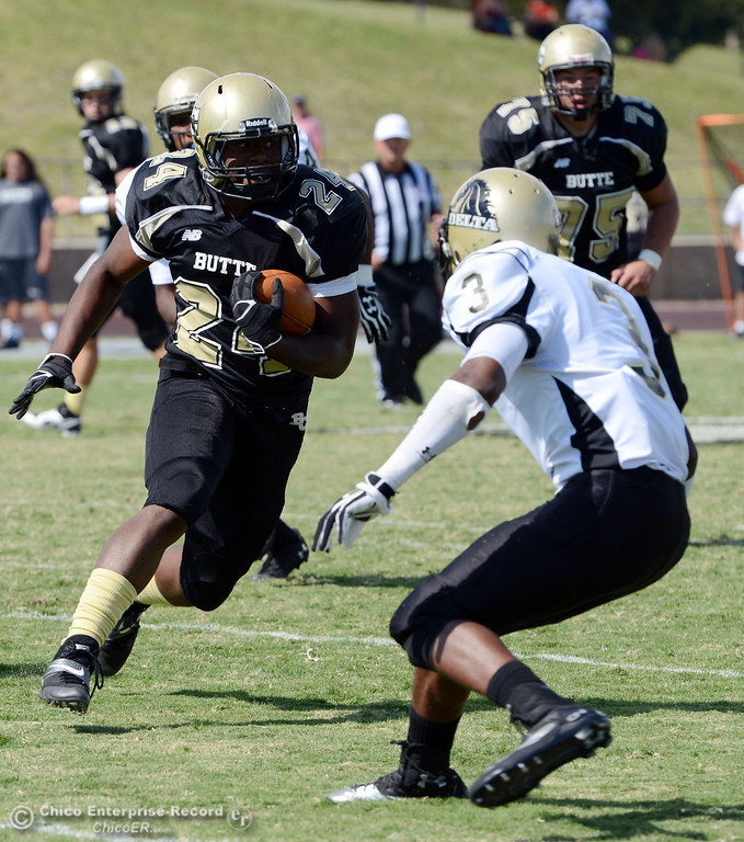 Description of . Butte Colleges' #24 Kendall Williams (left) rushes against Delta College's #3 SynJohn Sears (right) in the second quarter of their football game at Butte's Cowan Stadium Saturday, September 28, 2013, in Oroville, Calif.  (Jason Halley/Chico Enterprise-Record)