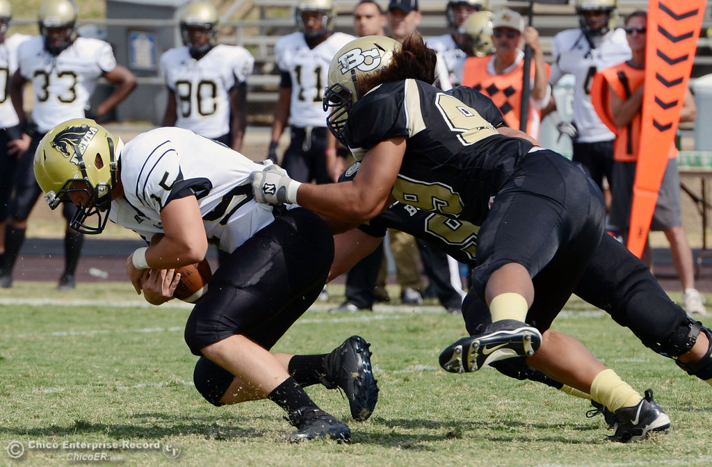Description of . Butte College\'s #99 Leopeni Siania (right) sacks against Delta College\'s #15 Cody Weinzheimer (left) in the second quarter of their football game at Butte\'s Cowan Stadium Saturday, September 28, 2013, in Oroville, Calif.  (Jason Halley/Chico Enterprise-Record)