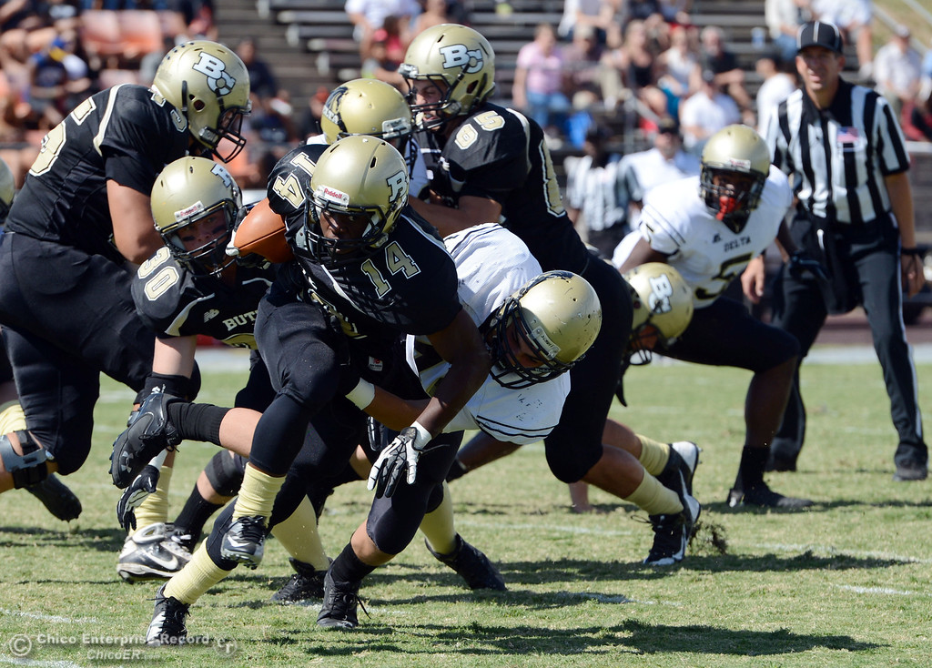 Description of . Butte College's #14 Robert Frazier (left) is tackled against Delta College's #40 Adrian Ramos (right) in the first quarter of their football game at Butte's Cowan Stadium Saturday, September 28, 2013, in Oroville, Calif.  (Jason Halley/Chico Enterprise-Record)