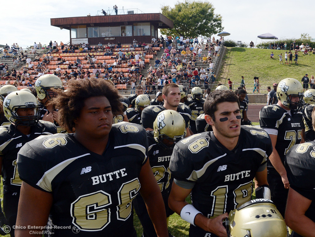 Description of . Butte College's #66 Paul Tablit III (left) and #18 Eric Ascensio (right) come off the field against Delta College at the end of the second quarter of their football game at Butte's Cowan Stadium Saturday, September 28, 2013, in Oroville, Calif.  (Jason Halley/Chico Enterprise-Record)
