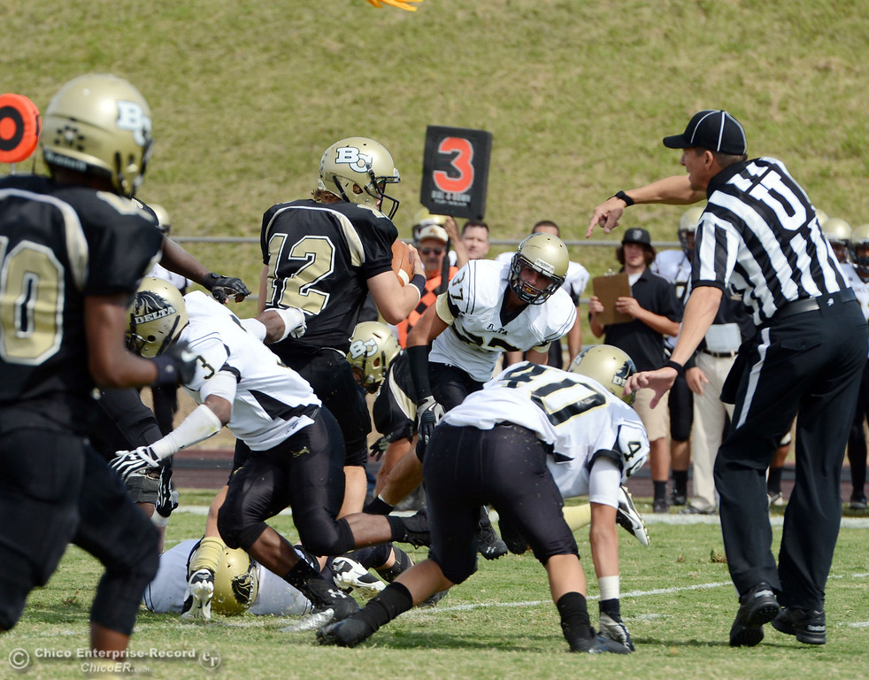 Description of . Butte College's #12 Thomas Stuart (center) is tackled against Delta College in the second quarter of their football game at Butte's Cowan Stadium Saturday, September 28, 2013, in Oroville, Calif.  (Jason Halley/Chico Enterprise-Record)