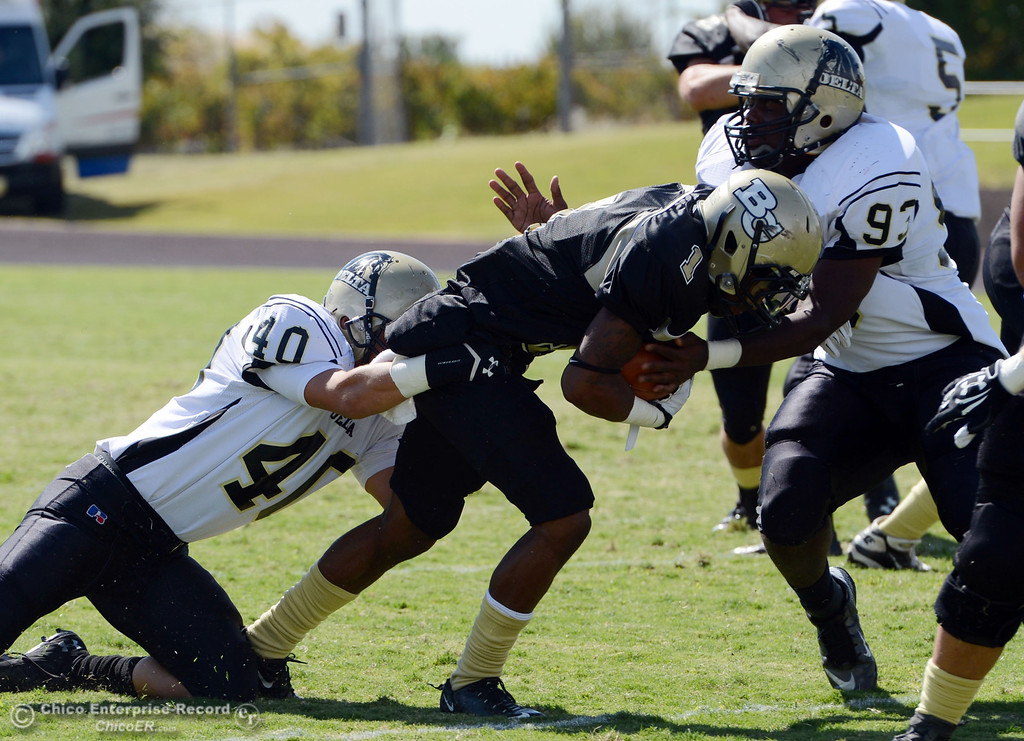 Description of . Butte College's #1 Wes McCoy (center) is tackled against Delta College's #40 Adrian Ramos (left) and #93 Marcus Brown (right) in the first quarter of their football game at Butte's Cowan Stadium Saturday, September 28, 2013, in Oroville, Calif.  (Jason Halley/Chico Enterprise-Record)