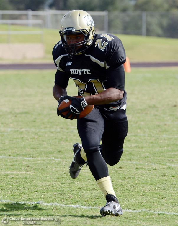 Description of . Butte College's #21 Marvel Harris rushes against Delta College in the fourth quarter of their football game at Butte's Cowan Stadium Saturday, September 28, 2013, in Oroville, Calif.  (Jason Halley/Chico Enterprise-Record)