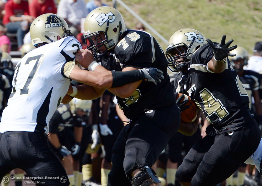 Description of . Butte Colleges' #24 Kendall Williams (right) rushes on a block by #75 Jacob Vazquez (center) against Delta College's #37 Chris Davi (left) in the second quarter of their football game at Butte's Cowan Stadium Saturday, September 28, 2013, in Oroville, Calif.  (Jason Halley/Chico Enterprise-Record)