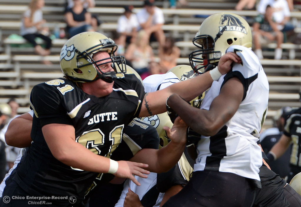 Description of . Butte College\'s #61 Jacob Bigham (left) pushes against Delta College\'s #5 SaShaun Perkins (right) in the fourth quarter of their football game at Butte\'s Cowan Stadium Saturday, September 28, 2013, in Oroville, Calif.  (Jason Halley/Chico Enterprise-Record)
