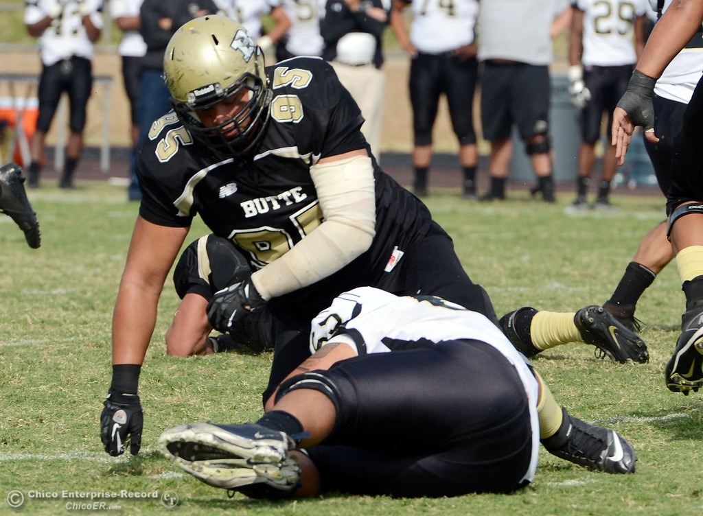 Description of . Butte College\'s #95 Mark Rosenquist (top) defends against Delta College\'s #16 JaVaughn Iverson (bottom)  in the fourth quarter of their football game at Butte\'s Cowan Stadium Saturday, September 28, 2013, in Oroville, Calif.  (Jason Halley/Chico Enterprise-Record)