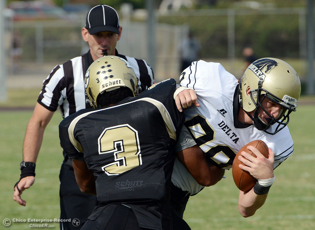 Description of . Butte College\'s #3 London Muse (left) tackles against Delta College\'s #89 Brian Golston (right) in the fourth quarter of their football game at Butte\'s Cowan Stadium Saturday, September 28, 2013, in Oroville, Calif.  (Jason Halley/Chico Enterprise-Record)