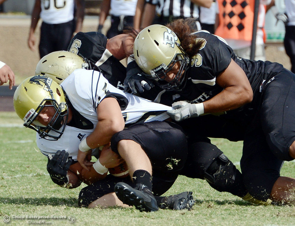 Description of . Butte College's #99 Leopeni Siania (right) and #9 Tyler Adair (back) sack against Delta College's #15 Cody Weinzheimer (left) in the second quarter of their football game at Butte's Cowan Stadium Saturday, September 28, 2013, in Oroville, Calif.  (Jason Halley/Chico Enterprise-Record)