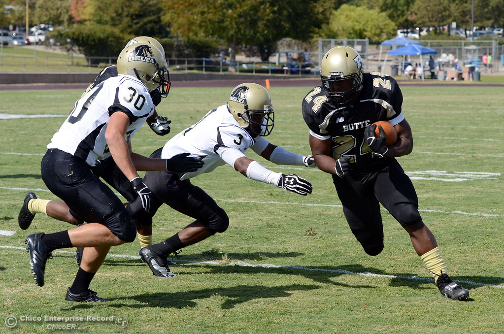 Description of . Butte Colleges' #24 Kendall Williams (right) rushes against Delta College's #3 SynJohn Sears (center) and #30 Andrew Traux (left) in the second quarter of their football game at Butte's Cowan Stadium Saturday, September 28, 2013, in Oroville, Calif.  (Jason Halley/Chico Enterprise-Record)