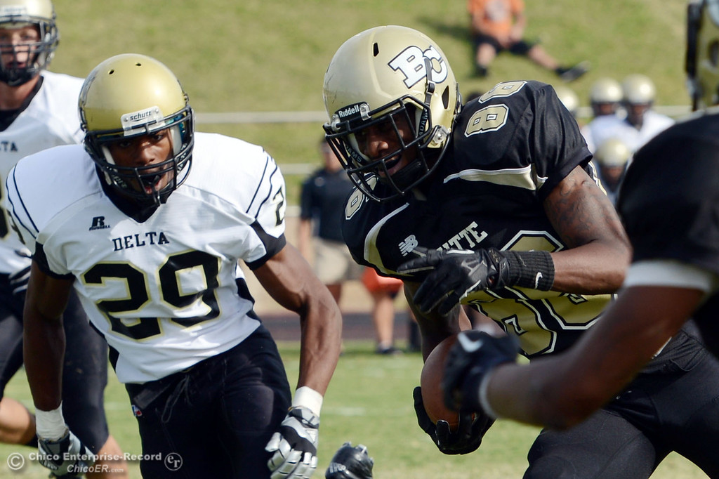 . Butte College\'s #86 Jon Parks (right) rushes for a touchdown against Delta College\'s #29 Damien Bell-White (left) in the fourth quarter of their football game at Butte\'s Cowan Stadium Saturday, September 28, 2013, in Oroville, Calif.  (Jason Halley/Chico Enterprise-Record)