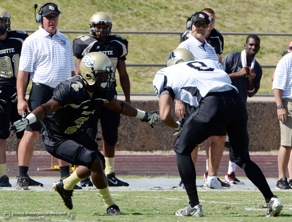 Description of . Butte College's #2 Deonte Flemings (left) tackles against Delta College's #8 William Mafi (right) in the first quarter of their football game at Butte's Cowan Stadium Saturday, September 28, 2013, in Oroville, Calif.  (Jason Halley/Chico Enterprise-Record)