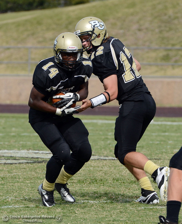 Description of . Butte College's #14 Robert Frazier (left) receives the handoff from #12 Thomas Stuart (right) against Delta College in the third quarter of their football game at Butte's Cowan Stadium Saturday, September 28, 2013, in Oroville, Calif.  (Jason Halley/Chico Enterprise-Record)