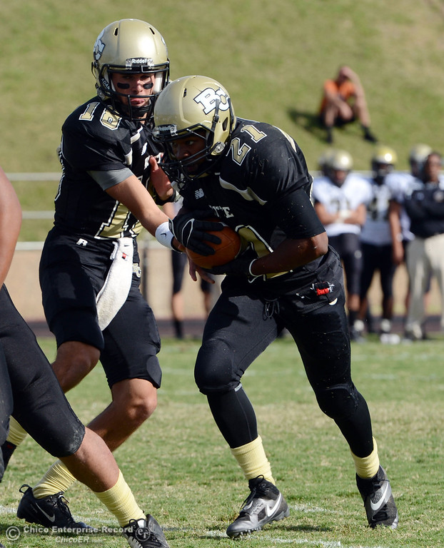 Description of . Butte College's #21 Marvel Harris (right) receives the handoff from #12 Thomas Stuart (center) against Delta College in the fourth quarter of their football game at Butte's Cowan Stadium Saturday, September 28, 2013, in Oroville, Calif.  (Jason Halley/Chico Enterprise-Record)
