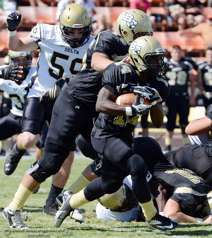 Description of . Butte College's #14 Robert Frazier (left) rushes against Delta College in the first quarter of their football game at Butte's Cowan Stadium Saturday, September 28, 2013, in Oroville, Calif.  (Jason Halley/Chico Enterprise-Record)