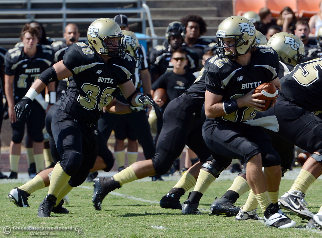 Description of . Butte College's #12 Thomas Stuart (right) drops back next to #30 Eric DeLucchi (left) against Delta College in the first quarter of their football game at Butte's Cowan Stadium Saturday, September 28, 2013, in Oroville, Calif.  (Jason Halley/Chico Enterprise-Record)