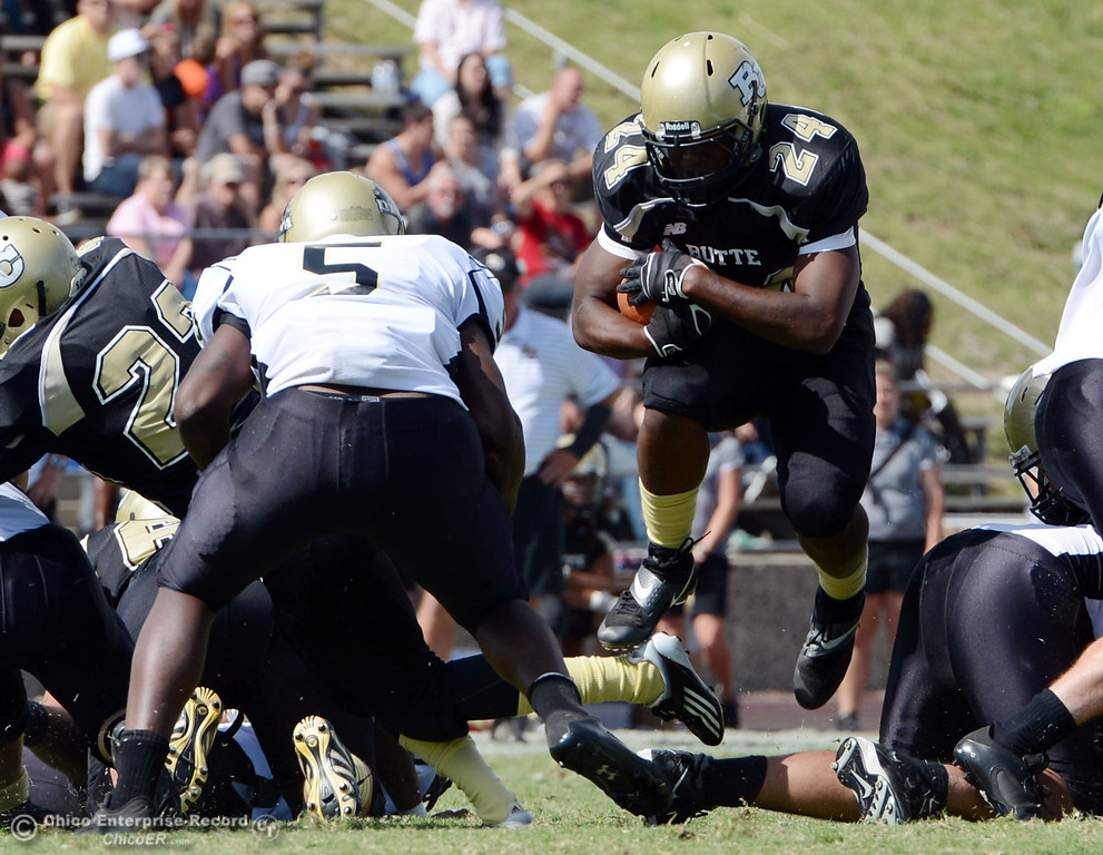 Description of . Butte College's #24 Kendall Williams (right) rushes against Delta College's #5 Daris Bishop (left) in the second quarter of their football game at Butte's Cowan Stadium Saturday, September 28, 2013, in Oroville, Calif.  (Jason Halley/Chico Enterprise-Record)
