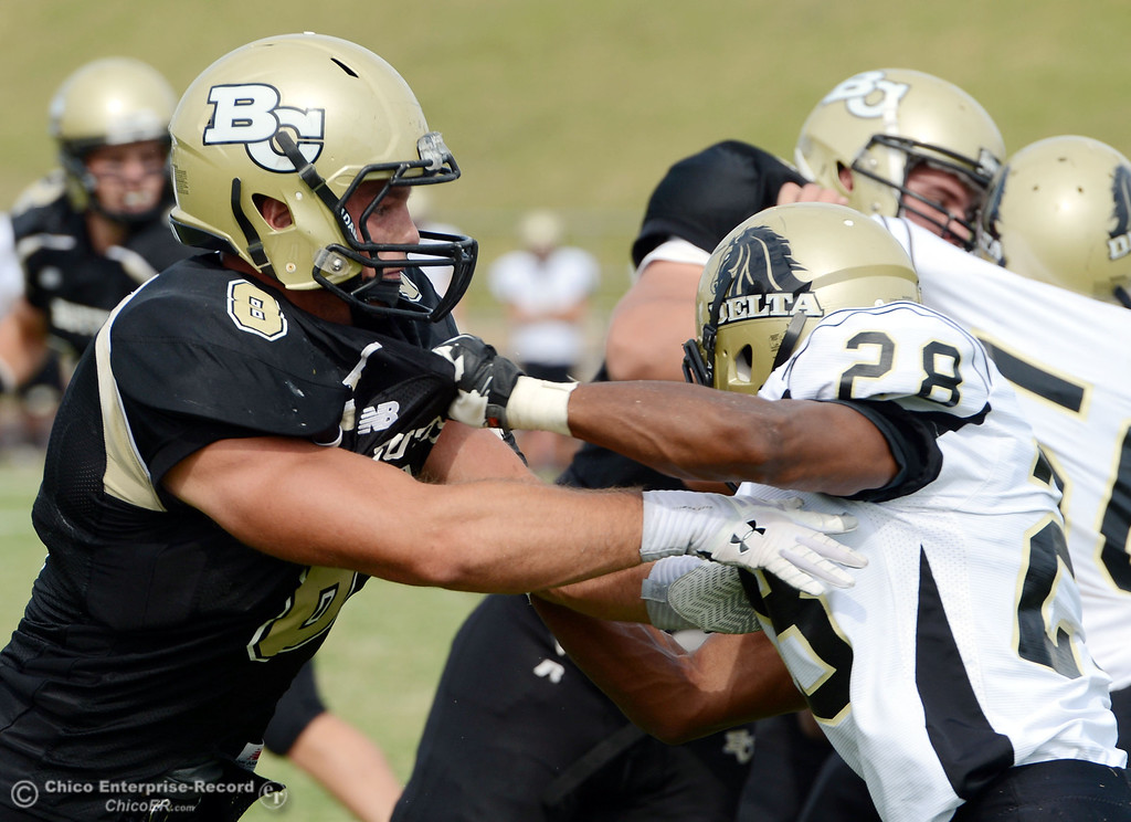 Description of . Butte College\'s #8 Bo Brummel (left) blocks against Delta College\'s #28 Robert Bivens (right) in the third quarter of their football game at Butte\'s Cowan Stadium Saturday, September 28, 2013, in Oroville, Calif.  (Jason Halley/Chico Enterprise-Record)