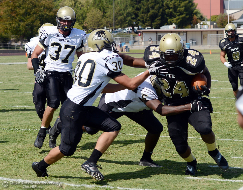 Description of . Butte Colleges' #24 Kendall Williams (right) rushes against Delta College's #5 DaShaun Perkins (center) #30 Andrew Traux (left) in the second quarter of their football game at Butte's Cowan Stadium Saturday, September 28, 2013, in Oroville, Calif.  (Jason Halley/Chico Enterprise-Record)