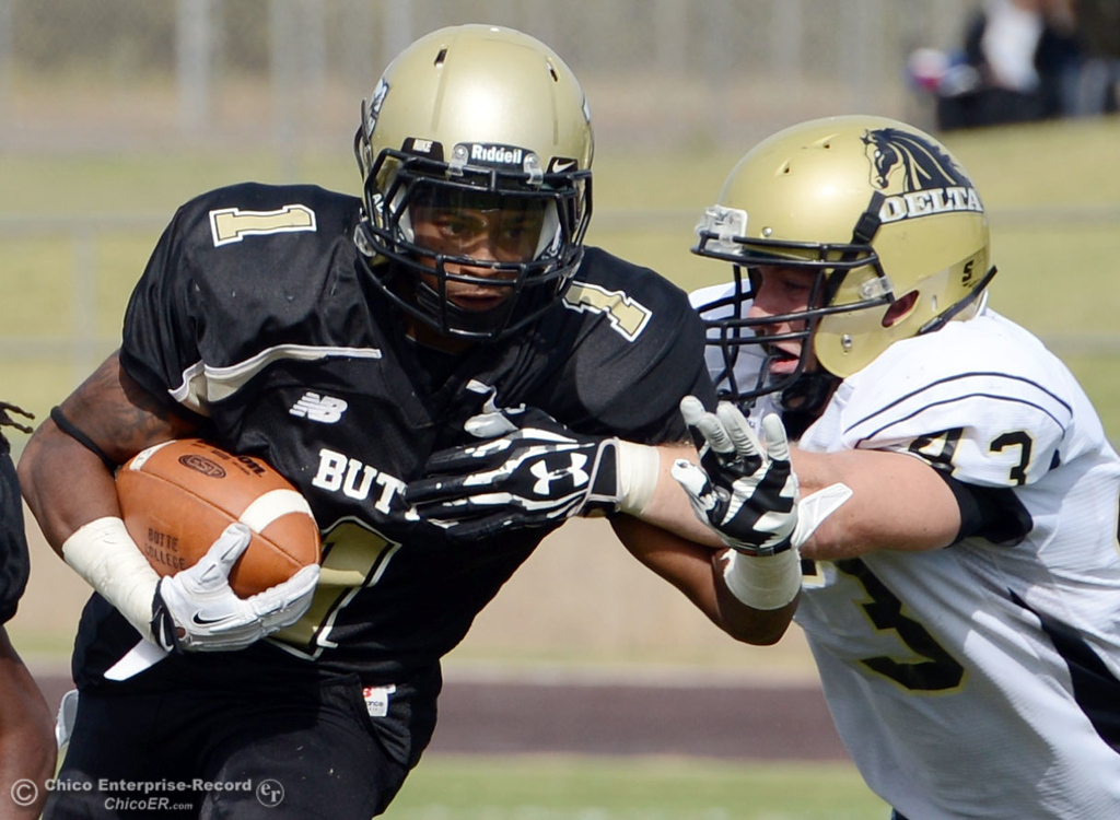 Description of . Butte College's #1 Wes McCoy (left) is tackled against Delta College's #43 James Christopherson (right) in the third quarter of their football game at Butte's Cowan Stadium Saturday, September 28, 2013, in Oroville, Calif.  (Jason Halley/Chico Enterprise-Record)