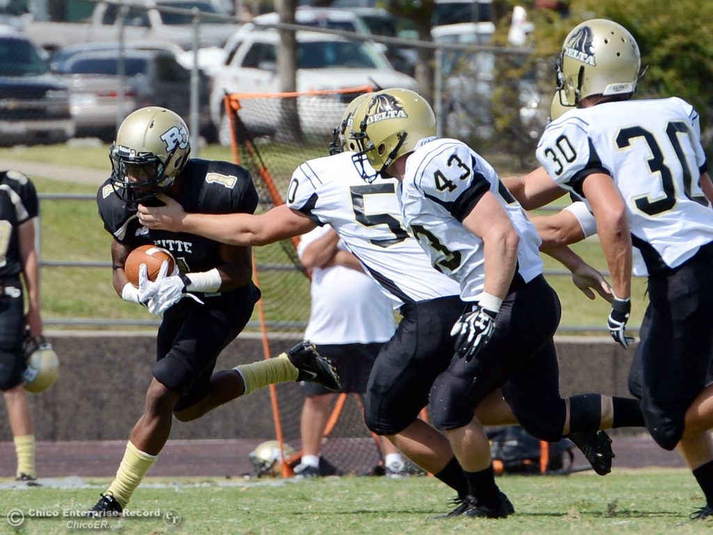 Description of . Butte College's #1 Wes McCoy (left) rushes against Delta College in the second quarter of their football game at Butte's Cowan Stadium Saturday, September 28, 2013, in Oroville, Calif.  (Jason Halley/Chico Enterprise-Record)