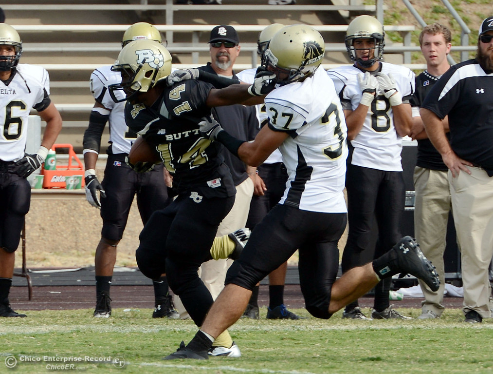 Description of . Butte College's #14 Robert Frazier (left) is tackled against Delta College's #37 Chris Davi (right) in the fourth quarter of their football game at Butte's Cowan Stadium Saturday, September 28, 2013, in Oroville, Calif.  (Jason Halley/Chico Enterprise-Record)
