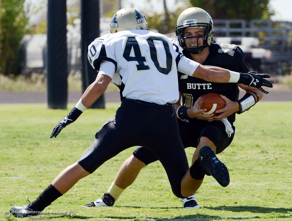 Description of . Butte College's #12 Thomas Stuart (right) scrambles against Delta College's #40 Adrian Ramos (left) in the first quarter of their football game at Butte's Cowan Stadium Saturday, September 28, 2013, in Oroville, Calif.  (Jason Halley/Chico Enterprise-Record)