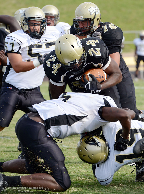 Description of . Butte College's #24 Kendall Williams (center) is tackled against Delta College in the fourth quarter of their football game at Butte's Cowan Stadium Saturday, September 28, 2013, in Oroville, Calif.  (Jason Halley/Chico Enterprise-Record)