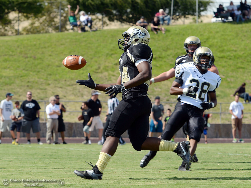 Description of . Butte Colleges' #24 Kendall Williams (left) rushes for a touchdown against Delta College's #28 Robert Bivens (right) in the second quarter of their football game at Butte's Cowan Stadium Saturday, September 28, 2013, in Oroville, Calif.  (Jason Halley/Chico Enterprise-Record)