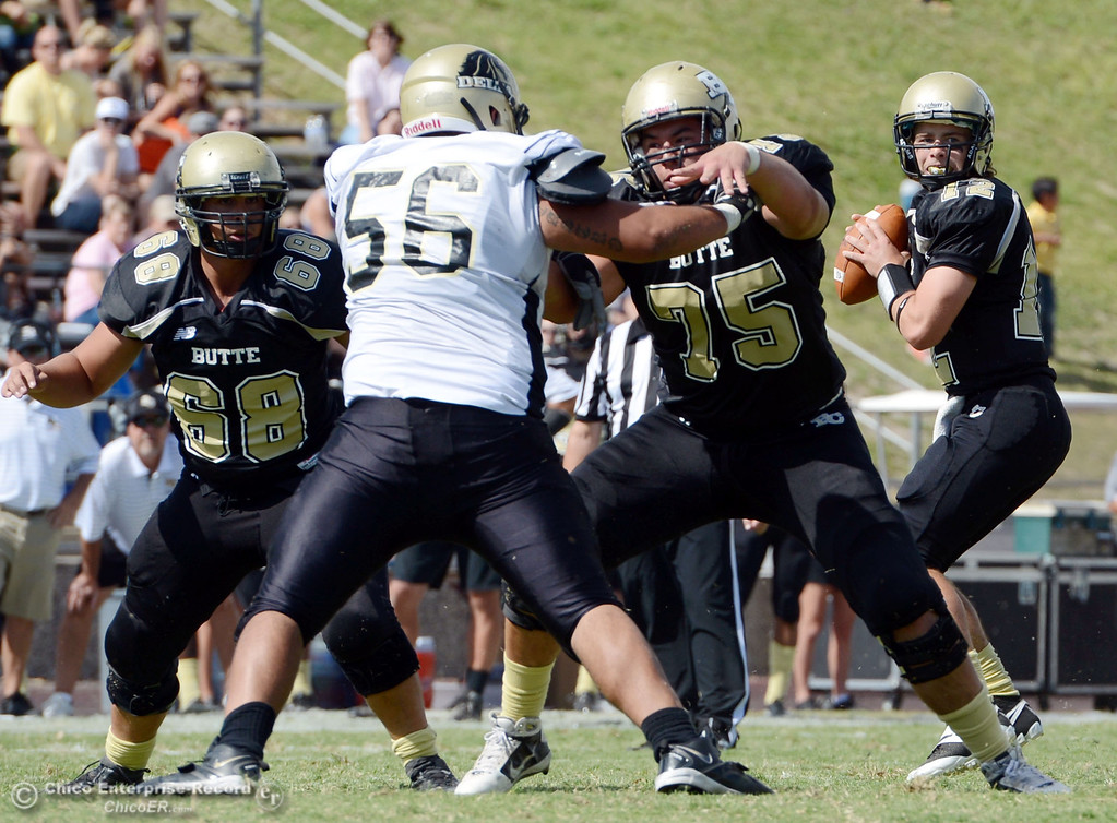 Description of . Butte College\'s #68 Eli Thom (left) and #75 Jacob Vazquez (right) block for #12 Thomas Stuart (far right) to pass against Delta College\'s #56 Sean Castro (center) in the second quarter of their football game at Butte\'s Cowan Stadium Saturday, September 28, 2013, in Oroville, Calif.  (Jason Halley/Chico Enterprise-Record)