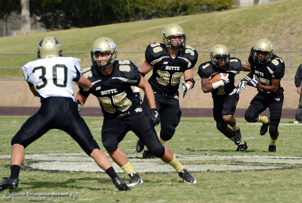 Description of . Butte College's #1 Wes McCoy (center) rushes against Delta College in the third quarter of their football game at Butte's Cowan Stadium Saturday, September 28, 2013, in Oroville, Calif.  (Jason Halley/Chico Enterprise-Record)