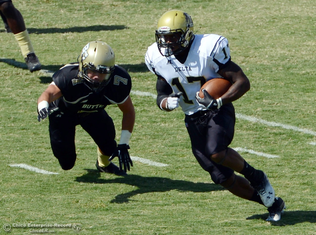 Description of . Butte College's #17 Peter Wysong (left) defends against Delta College's #17 Theo Wooford (right) in the first quarter of their football game at Butte's Cowan Stadium Saturday, September 28, 2013, in Oroville, Calif.  (Jason Halley/Chico Enterprise-Record)