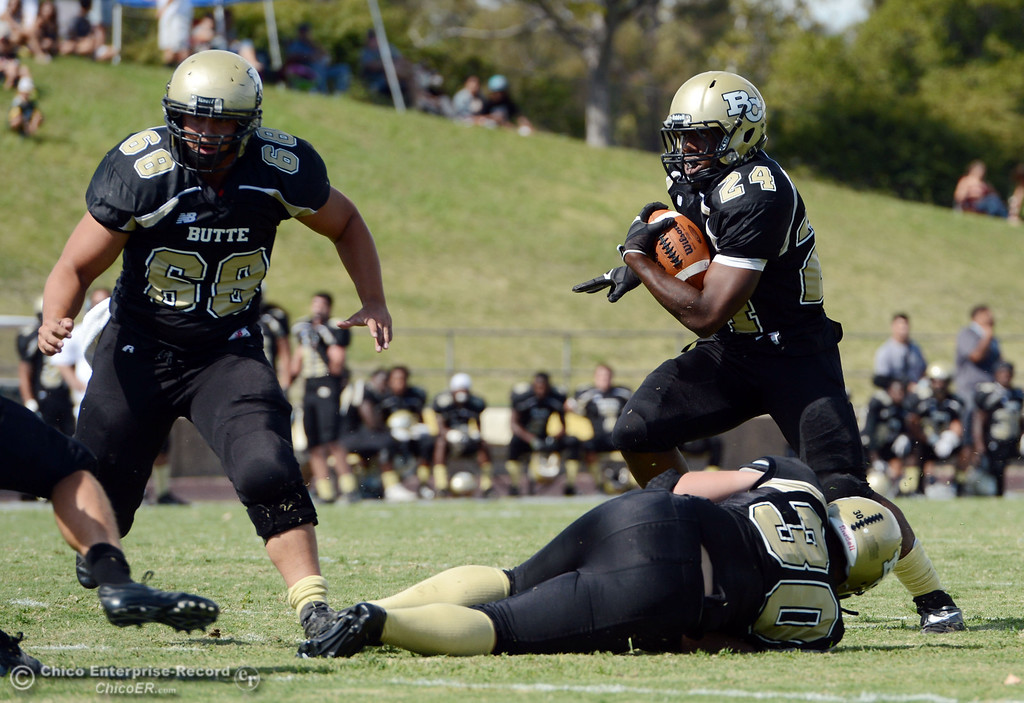 Description of . Butte Colleges' #24 Kendall Williams (right) rushes for a touchdown behind #30 Eri DeLucchi (bottom) and #68 Eli Thom (left) against Delta College in the second quarter of their football game at Butte's Cowan Stadium Saturday, September 28, 2013, in Oroville, Calif.  (Jason Halley/Chico Enterprise-Record)