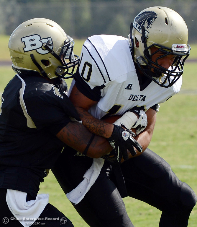Description of . Butte College\'s #1 Wes McCoy (left) tackles against Delta College\'s #10 Anthony Wills (right) in the second quarter of their football game at Butte\'s Cowan Stadium Saturday, September 28, 2013, in Oroville, Calif.  (Jason Halley/Chico Enterprise-Record)