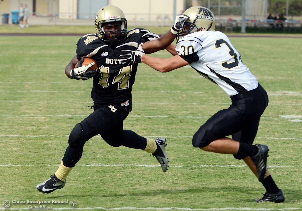 Description of . Butte Colleges' #14 Robert Frazier (left) is tackled against Delta College's #30 Andrew Truaz (right ) in the third quarter of their football game at Butte's Cowan Stadium Saturday, September 28, 2013, in Oroville, Calif.  (Jason Halley/Chico Enterprise-Record)