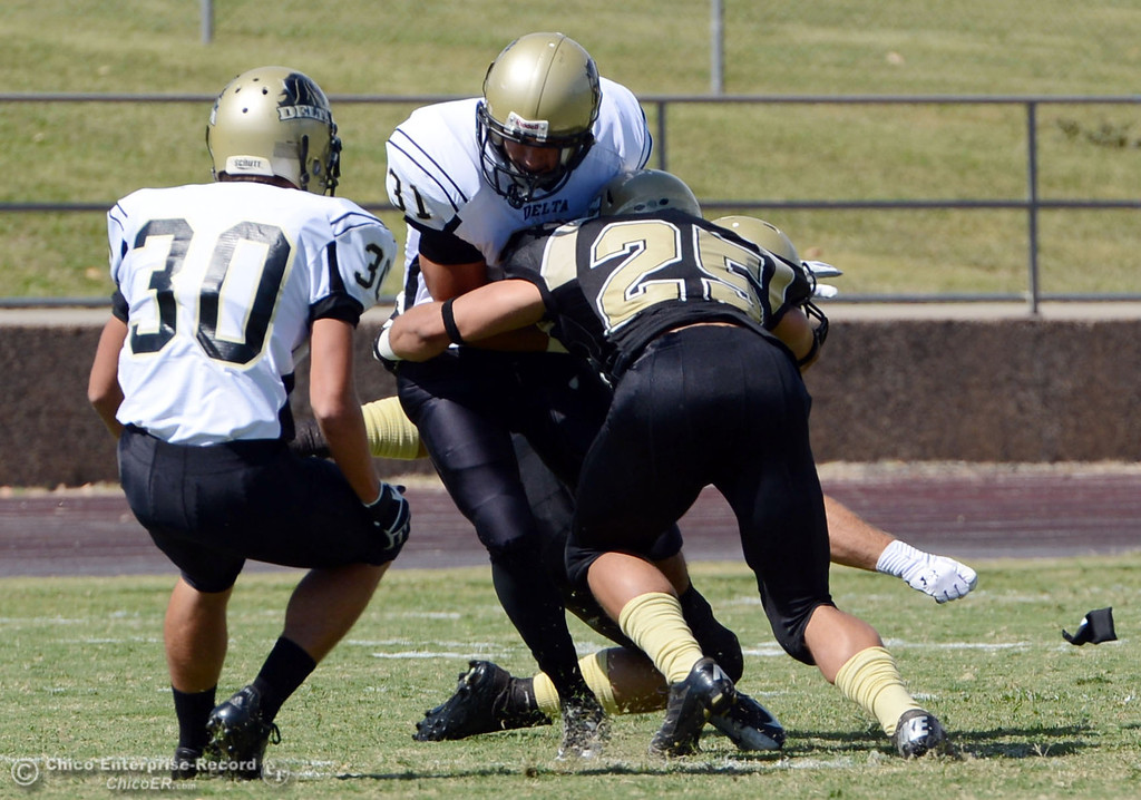 Description of . Butte College\'s #25 De\'Aundray Gooden (right) tackles against Delta College\'s #31 Brian Wood (center) as #30 Andrew Traux (left) looks on in the first quarter of their football game at Butte\'s Cowan Stadium Saturday, September 28, 2013, in Oroville, Calif.  (Jason Halley/Chico Enterprise-Record)