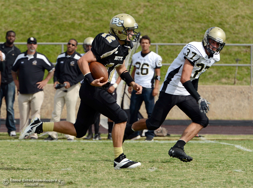 Description of . Butte College's #12 Thomas Stuart (left) carries for a quarterback sneak touchdown against Delta College's #37 Chris Davi (right) in the third quarter of their football game at Butte's Cowan Stadium Saturday, September 28, 2013, in Oroville, Calif.  (Jason Halley/Chico Enterprise-Record)