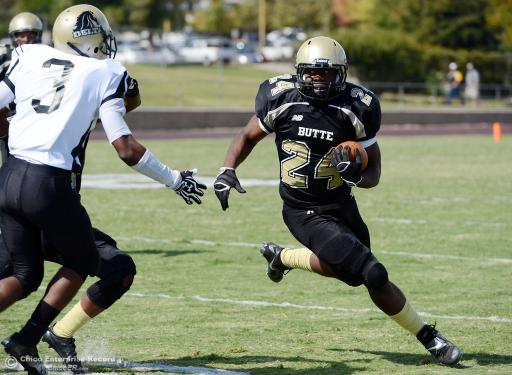 Description of . Butte Colleges' #24 Kendall Williams (right) rushes against Delta College's #3 SynJohn Sears (left) in the second quarter of their football game at Butte's Cowan Stadium Saturday, September 28, 2013, in Oroville, Calif.  (Jason Halley/Chico Enterprise-Record)