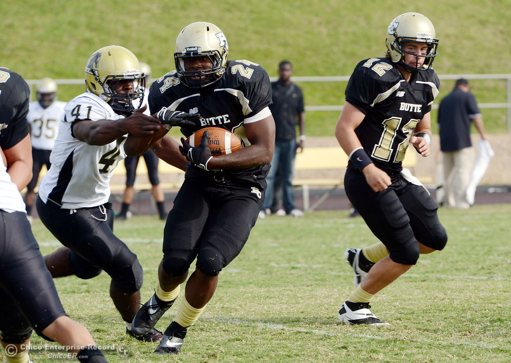 Description of . Butte College's #12 Thomas Stuart (right) watches #24 Kendall Williams (center) rush against Delta College's #41 Richard Black (left) in the fourth quarter of their football game at Butte's Cowan Stadium Saturday, September 28, 2013, in Oroville, Calif.  (Jason Halley/Chico Enterprise-Record)
