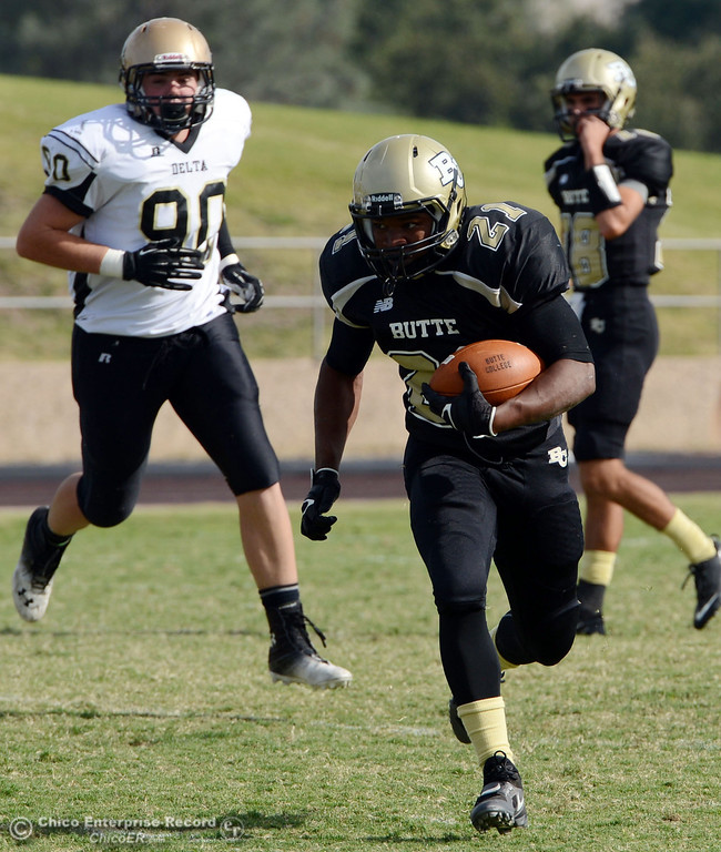 Description of . Butte College's #21 Marvel Harris (right) rushes against Delta College's #90 Logan Finley (left) in the fourth quarter of their football game at Butte's Cowan Stadium Saturday, September 28, 2013, in Oroville, Calif.  (Jason Halley/Chico Enterprise-Record)