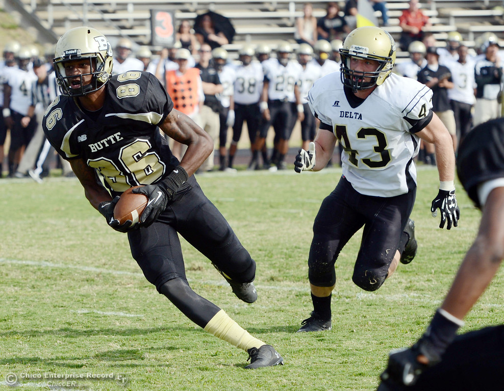 Description of . Butte College's #86 Jon Parks (left) rushes for a touchdown against Delta College's #43 James Christopherson (right) in the fourth quarter of their football game at Butte's Cowan Stadium Saturday, September 28, 2013, in Oroville, Calif.  (Jason Halley/Chico Enterprise-Record)