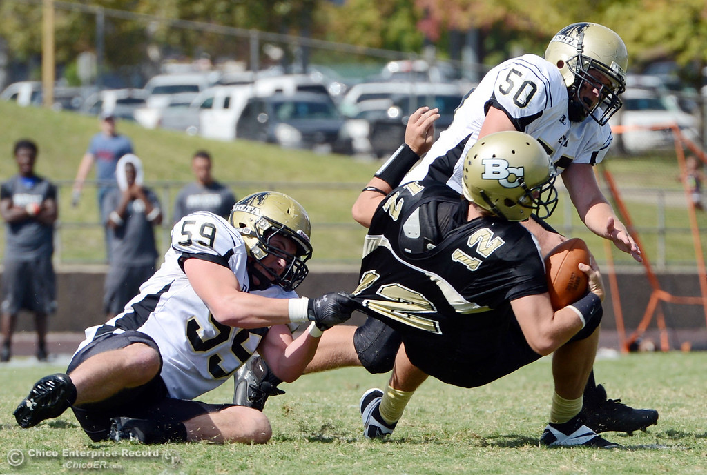 Description of . Butte College\'s #12 Thomas Stuart (center) is sacked against Delta College\'s #59 Nathan DiDonato (left) and #50 Tyler Huckaby (right)in the second quarter of their football game at Butte\'s Cowan Stadium Saturday, September 28, 2013, in Oroville, Calif.  (Jason Halley/Chico Enterprise-Record)