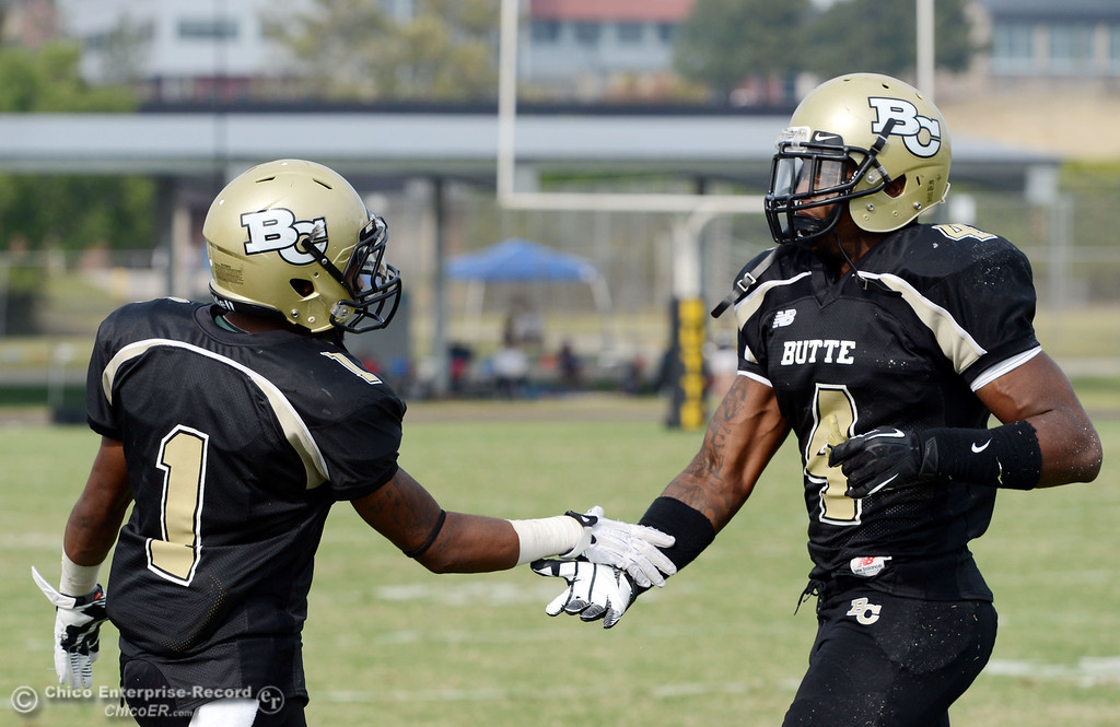 Description of . Butte College's #1 Wes McCoy (left) takes #4 Chris Edwards (right) off the field against Delta College in the fourth quarter of their football game at Butte's Cowan Stadium Saturday, September 28, 2013, in Oroville, Calif.  (Jason Halley/Chico Enterprise-Record)