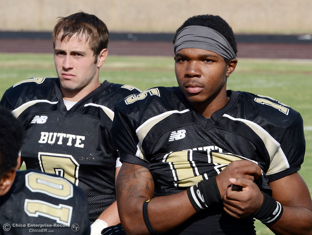 Description of . Butte College\'s #7 Ryan Holland (left) and #15 Jalen Amis (right) listen to the team meeting against Delta College at the end of their football game at Butte\'s Cowan Stadium Saturday, September 28, 2013, in Oroville, Calif.  (Jason Halley/Chico Enterprise-Record)