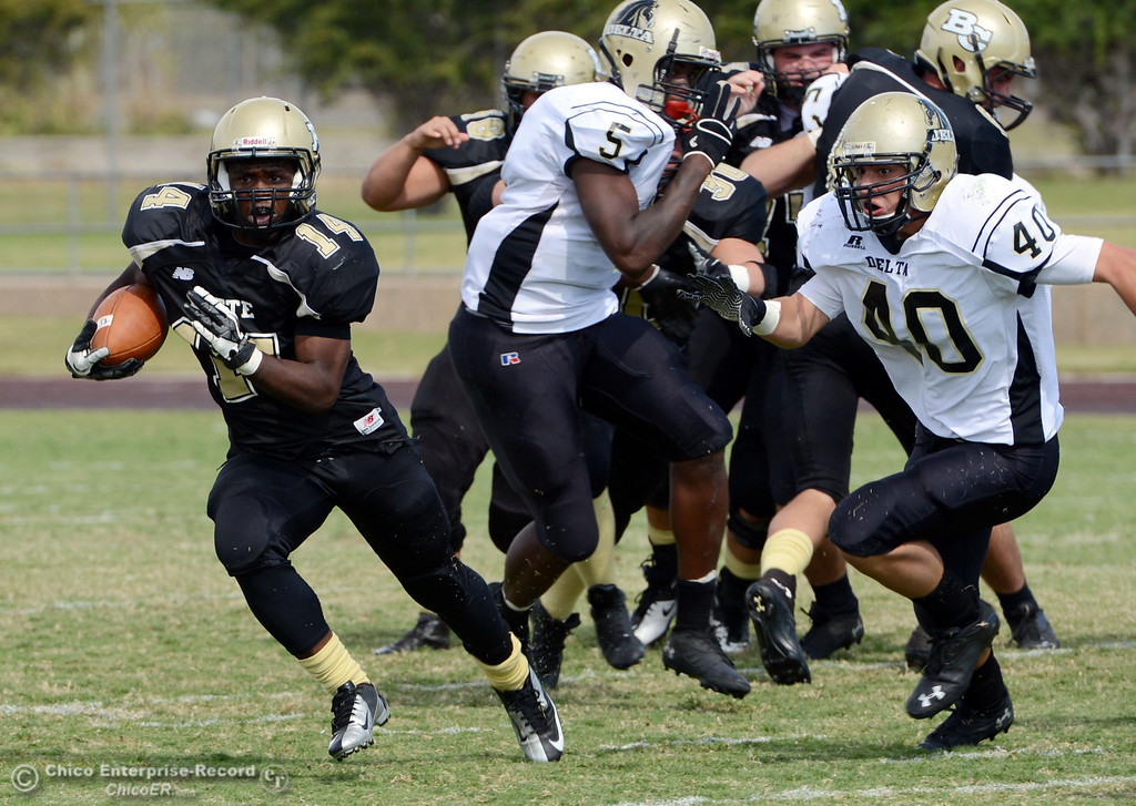 Description of . Butte College's #14 Robert Frazier (left) rushes on a block against Delta College's #40 Adrian Ramos (right) in the second quarter of their football game at Butte's Cowan Stadium Saturday, September 28, 2013, in Oroville, Calif.  (Jason Halley/Chico Enterprise-Record)
