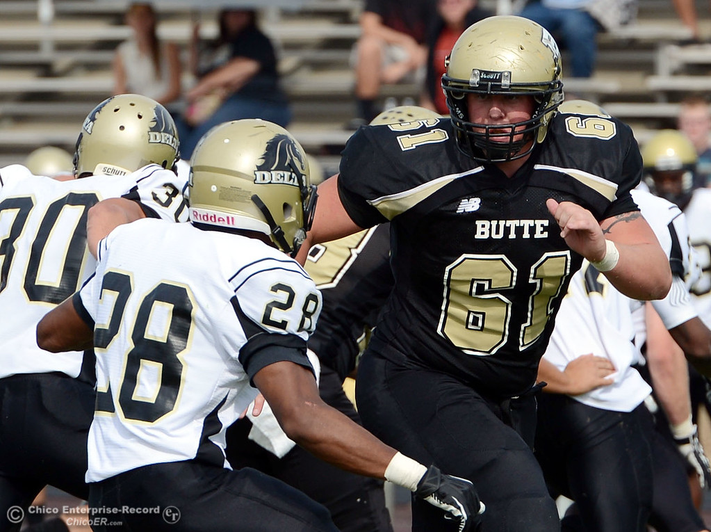 Description of . Butte College's #61 Jacob Bigham (right) blocks against Delta College's #28 Robert Bivens (left) in the third quarter of their football game at Butte's Cowan Stadium Saturday, September 28, 2013, in Oroville, Calif.  (Jason Halley/Chico Enterprise-Record)