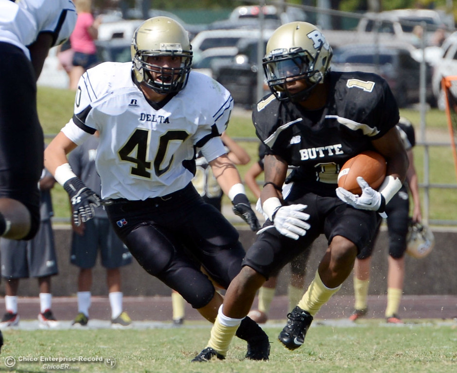 Description of . Butte College's #1 Wes McCoy (right) rushes against Delta College's #40 Adrian Ramos (left) in the second quarter of their football game at Butte's Cowan Stadium Saturday, September 28, 2013, in Oroville, Calif.  (Jason Halley/Chico Enterprise-Record)