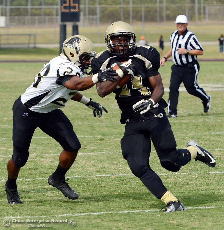 Description of . Butte Colleges' #14 Robert Frazier (right) breaks a tackle against Delta College's #28 Robert Bivens (left) in the third quarter of their football game at Butte's Cowan Stadium Saturday, September 28, 2013, in Oroville, Calif.  (Jason Halley/Chico Enterprise-Record)