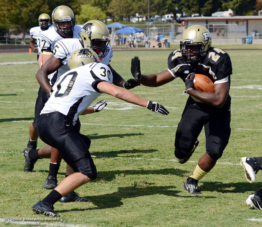 Description of . Butte Colleges\' #24 Kendall Williams (right) rushes against Delta College\'s #5 DaShaun Perkins (center) #30 Andrew Traux (left) in the second quarter of their football game at Butte\'s Cowan Stadium Saturday, September 28, 2013, in Oroville, Calif.  (Jason Halley/Chico Enterprise-Record)