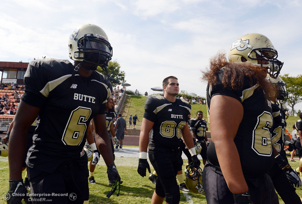 Description of . Butte College's #6 Denzel Conyers, #68 Eli Thom, and #64 Jess Savusa (left to right) come off the field against Delta College at the end of the second quarter of their football game at Butte's Cowan Stadium Saturday, September 28, 2013, in Oroville, Calif.  (Jason Halley/Chico Enterprise-Record)