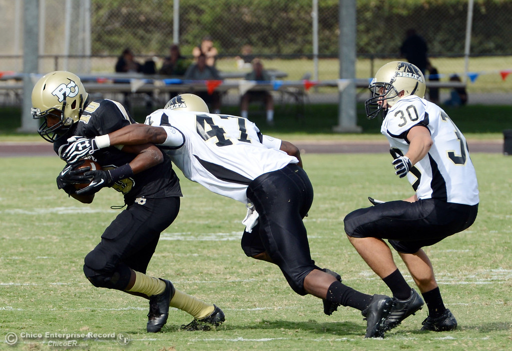 Description of . Butte College's #10 CJ Grice (left) breaks the tackle against Delta College's #47 LeeAndre Fisher (center) and #30 Andrew Truaz (right) in the third quarter of their football game at Butte's Cowan Stadium Saturday, September 28, 2013, in Oroville, Calif.  (Jason Halley/Chico Enterprise-Record)